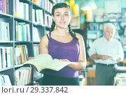 Купить «Young pretty girl customer is choosing new book», фото № 29337842, снято 28 июня 2017 г. (c) Яков Филимонов / Фотобанк Лори