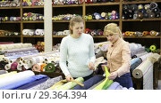 Купить «Portrait of positive salesgirl working in fabrics store, offering advice to young female client», видеоролик № 29364394, снято 28 марта 2018 г. (c) Яков Филимонов / Фотобанк Лори