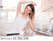 Купить «Portrait of sporty female who is standing near laptop and doing exercises», фото № 29366546, снято 19 апреля 2018 г. (c) Яков Филимонов / Фотобанк Лори
