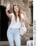 Купить «Female traveler with luggage doing selfie», фото № 29366694, снято 17 мая 2017 г. (c) Яков Филимонов / Фотобанк Лори