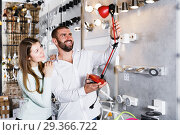 Купить «Smiling couple customers trying use modern desk lamp», фото № 29366722, снято 29 января 2018 г. (c) Яков Филимонов / Фотобанк Лори
