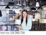Купить «Smiling woman customer choosing torchere in store», фото № 29366726, снято 29 января 2018 г. (c) Яков Филимонов / Фотобанк Лори