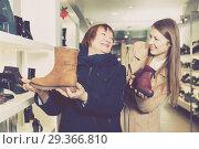 Купить «Young smiling female and her mother are choosing modern ankle boots», фото № 29366810, снято 13 декабря 2017 г. (c) Яков Филимонов / Фотобанк Лори