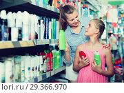 Купить «positive woman with girl choosing shampoo and conditioner», фото № 29366970, снято 5 августа 2017 г. (c) Яков Филимонов / Фотобанк Лори