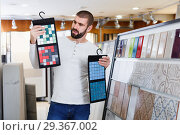 Купить «Positive man holding sample of kitchen ceramic tile in modern store», фото № 29367002, снято 2 февраля 2018 г. (c) Яков Филимонов / Фотобанк Лори