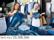 Купить «Two positive girls choosing denim trousers», фото № 29368366, снято 19 января 2019 г. (c) Яков Филимонов / Фотобанк Лори