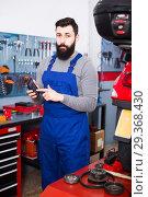 Купить «Worker considers the cost of repairing the motorcycle», фото № 29368430, снято 12 декабря 2018 г. (c) Яков Филимонов / Фотобанк Лори
