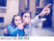 Купить «Positive mother pointing to daughter new sight», фото № 29368454, снято 16 декабря 2018 г. (c) Яков Филимонов / Фотобанк Лори