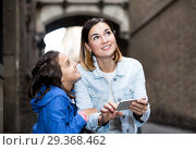 Купить «Mother and daughter consulting guide in phone», фото № 29368462, снято 16 декабря 2018 г. (c) Яков Филимонов / Фотобанк Лори