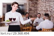 Купить «Smiling woman waitress carrying order for guest», фото № 29368494, снято 17 января 2017 г. (c) Яков Филимонов / Фотобанк Лори