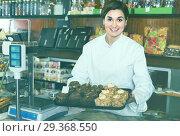 Купить «Woman seller showing tray of drizzled cakes», фото № 29368550, снято 24 января 2017 г. (c) Яков Филимонов / Фотобанк Лори