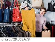 Купить «Smiling woman choosing turtleneck sweater», фото № 29368678, снято 7 февраля 2017 г. (c) Яков Филимонов / Фотобанк Лори