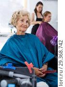 Купить «Elderly female client waiting for hair styling», фото № 29368742, снято 26 июня 2018 г. (c) Яков Филимонов / Фотобанк Лори
