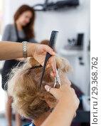 Купить «Hands of hairdresser making hairstyle for female», фото № 29368762, снято 26 июня 2018 г. (c) Яков Филимонов / Фотобанк Лори