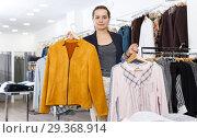 Купить «Woman holding lot of hanger with clothes», фото № 29368914, снято 10 октября 2018 г. (c) Яков Филимонов / Фотобанк Лори