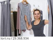Woman trying various clothes in dressing room. Стоковое фото, фотограф Яков Филимонов / Фотобанк Лори