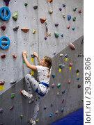 Купить «Teenage Caucasian girl climbing wall with holding safety rope, indoor», фото № 29382806, снято 7 октября 2018 г. (c) Кекяляйнен Андрей / Фотобанк Лори