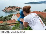 Купить «Женщина смотрит в телескоп на остров Свети Стефан с обзорной площадки. Черногория», фото № 29382842, снято 3 июня 2016 г. (c) Кекяляйнен Андрей / Фотобанк Лори
