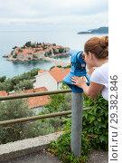 Observing place with coin operated binoculars in Sveti Stefan town. Woman looking at island in Adriatic sea, Montenegro, Europe (2016 год). Стоковое фото, фотограф Кекяляйнен Андрей / Фотобанк Лори