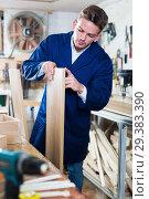 Guy woodworker adjusting chipboard at workplace. Стоковое фото, фотограф Яков Филимонов / Фотобанк Лори