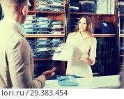 Купить «Female shopping assistant offering various shirts in men's cloths store», фото № 29383454, снято 26 марта 2019 г. (c) Яков Филимонов / Фотобанк Лори