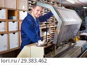 Купить «Male worker using machine for trimming at workshop», фото № 29383462, снято 7 ноября 2016 г. (c) Яков Филимонов / Фотобанк Лори