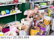 Купить «Female woman looking through different treats for dogs», фото № 29383494, снято 20 января 2019 г. (c) Яков Филимонов / Фотобанк Лори