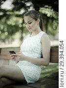 Купить «girl sitting on a bench and using mobile in garden», фото № 29394054, снято 8 июня 2017 г. (c) Яков Филимонов / Фотобанк Лори