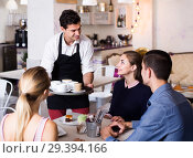 Купить «Polite smiling waiter bringing ordered dishes to friends in tearoom», фото № 29394166, снято 5 июня 2017 г. (c) Яков Филимонов / Фотобанк Лори