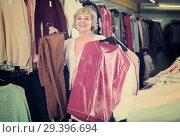 Купить «woman holding jumper, pants and jacket», фото № 29396694, снято 20 декабря 2017 г. (c) Яков Филимонов / Фотобанк Лори