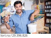 Купить «Man standing amongst racks in paint store with brushes and paint», фото № 29396826, снято 13 сентября 2017 г. (c) Яков Филимонов / Фотобанк Лори