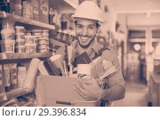 Купить «Workman holding basket with picked tools in paint store», фото № 29396834, снято 13 сентября 2017 г. (c) Яков Филимонов / Фотобанк Лори