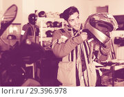 Купить «Man in moto jacket is choosing new helmet for motorbike in the store.», фото № 29396978, снято 1 сентября 2017 г. (c) Яков Филимонов / Фотобанк Лори