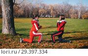 Купить «Two young woman in sport costumes doing leg lunges in park», видеоролик № 29397334, снято 23 июля 2019 г. (c) Константин Шишкин / Фотобанк Лори