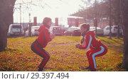 Купить «Two young woman in sport costumes doing squats in park», видеоролик № 29397494, снято 23 июля 2019 г. (c) Константин Шишкин / Фотобанк Лори