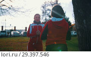 Купить «Two young woman in sport costumes doing squats in park in front of each other», видеоролик № 29397546, снято 23 июля 2019 г. (c) Константин Шишкин / Фотобанк Лори