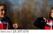 Купить «Two young woman in sport costumes doing exercises in park. Close up», видеоролик № 29397670, снято 23 июля 2019 г. (c) Константин Шишкин / Фотобанк Лори