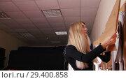Купить «Young woman at sewing factory. A woman puts a template on the wall.», видеоролик № 29400858, снято 10 декабря 2018 г. (c) Константин Шишкин / Фотобанк Лори
