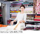 Купить «Seller showing white fabric», фото № 29405778, снято 4 января 2017 г. (c) Яков Филимонов / Фотобанк Лори