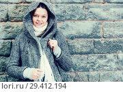 Купить «cheerful female in coat hood near wall», фото № 29412194, снято 11 ноября 2017 г. (c) Яков Филимонов / Фотобанк Лори
