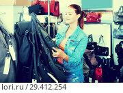 Купить «Girl buying handbag in fashion shop», фото № 29412254, снято 15 сентября 2016 г. (c) Яков Филимонов / Фотобанк Лори