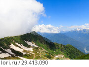 Panorama of the mountains and Aibga Ridge with low clouds. Remnants of snow and new green grass on Mountains near the ski resort of Rosa Khutor in Krasnaya Polyana. Sochi, Russia. Стоковое фото, фотограф Mikhail Starodubov / Фотобанк Лори