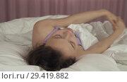 Купить «Beautiful teen girl wakes up in bed and smiles stock footage video», видеоролик № 29419882, снято 7 ноября 2018 г. (c) Юлия Машкова / Фотобанк Лори