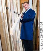 Купить «workman standing with wooden plank», фото № 29420454, снято 19 марта 2019 г. (c) Яков Филимонов / Фотобанк Лори