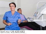 Купить «dentist female in uniform with visitor», фото № 29420682, снято 10 октября 2017 г. (c) Яков Филимонов / Фотобанк Лори