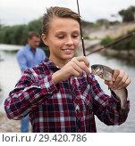 Купить «teenager boy holding catch fish on hook», фото № 29420786, снято 17 сентября 2016 г. (c) Яков Филимонов / Фотобанк Лори