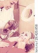 Купить «Happy woman examining result of beauty procedures», фото № 29420858, снято 26 апреля 2019 г. (c) Яков Филимонов / Фотобанк Лори