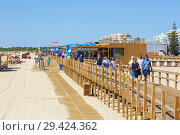 Wooden boardwalk promenade along the beach at Monte Gordo, Algarve, Portugal. (2018 год). Редакционное фото, фотограф Findlay Rankin / age Fotostock / Фотобанк Лори