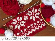 Купить «Needlework. Knit a red warm scarf with white snowflakes. Knitting needles and wool yarn on a wooden background», фото № 29427590, снято 19 июля 2018 г. (c) Виктория Катьянова / Фотобанк Лори