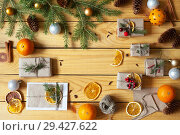 Купить «Hand-made Christmas gifts and greetings in envelopes decorated with dry orange slices and Christmas-tree branches with balls on a wooden background. New Year's still life», фото № 29427622, снято 25 июля 2018 г. (c) Виктория Катьянова / Фотобанк Лори